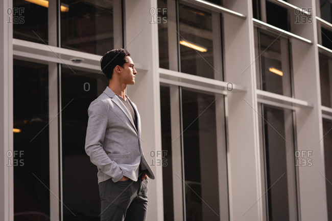 Front view of thoughtful Asian man standing near building