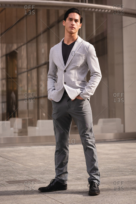 Front view of thoughtful handsome Asian man standing near building pavement