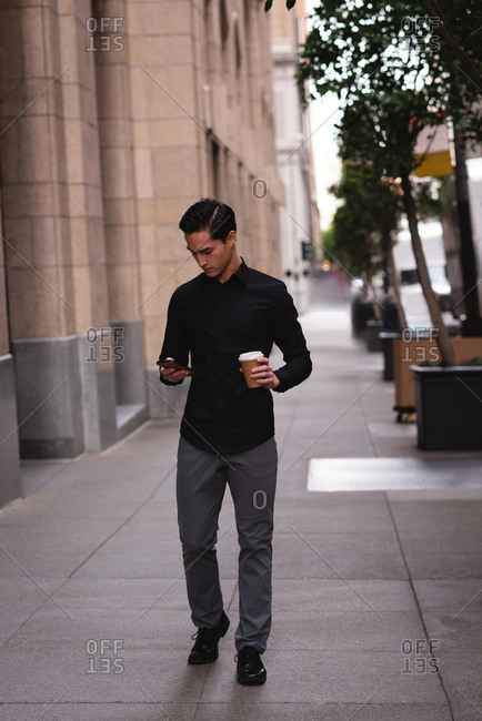 Front view of handsome Asian man using mobile phone with coffee while walking from street