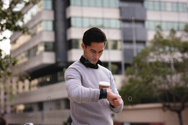 Front view of handsome Asian man using smart watch while having coffee on street