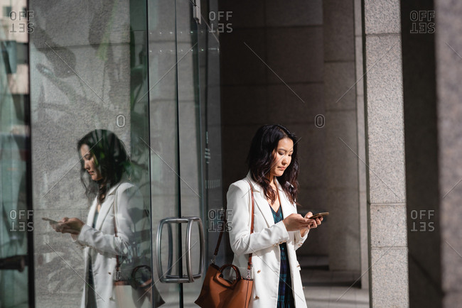Side view of beautiful Asian woman using mobile phone while standing in corridor