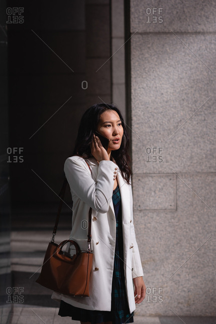 Side view of beautiful Asian woman talking on mobile phone while standing in corridor