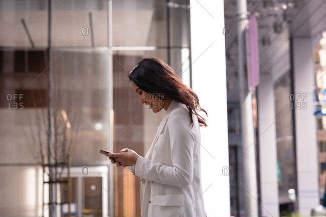 Side view of beautiful Asian woman using mobile phone while standing in a glass corridor