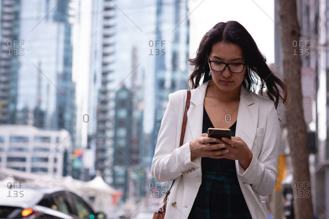 Front view of beautiful Asian woman with glasses using her mobile phone while walking in the street on a sunny day