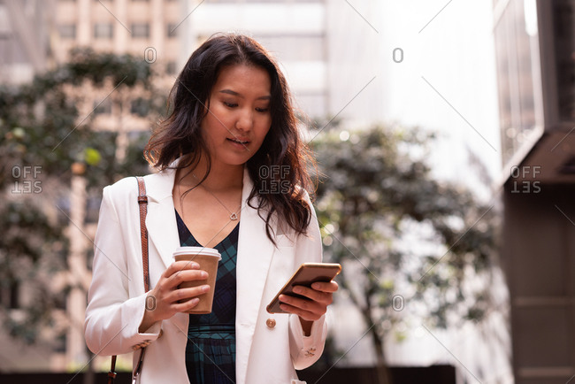Front view of beautiful Asian woman using mobile phone while standing in the street