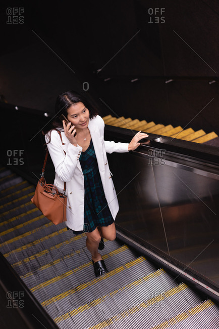 High angle view of pretty Asian woman talking on mobile phone on escalator
