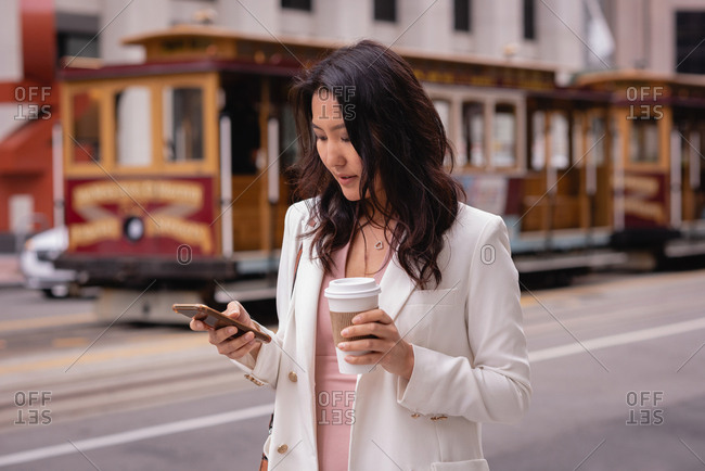 Front view of thoughtful beautiful Asian woman using mobile phone while having coffee at street