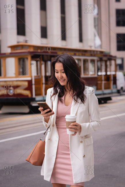 Front view of happy beautiful Asian woman smiling and using her mobile phone while having coffee at street