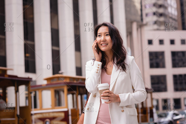 Front view of happy beautiful Asian woman talking on mobile phone while having coffee on street