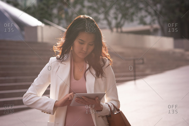 Front view of beautiful Asian woman using digital tablet while standing on pavement on a sunny day