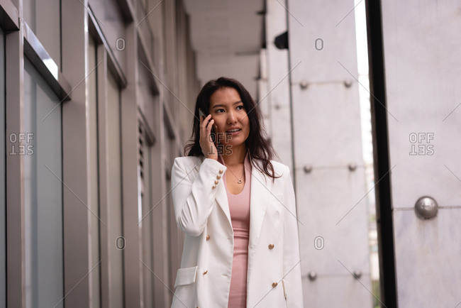 Front view of beautiful Asian woman talking on mobile phone while walking in corridor