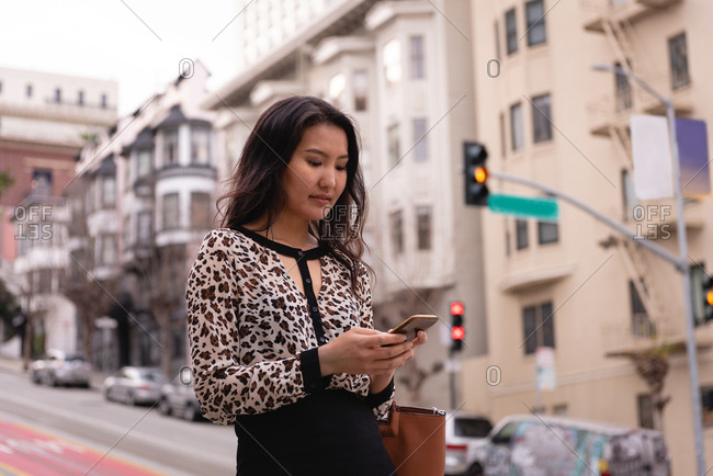 Side view of beautiful Asian woman using mobile phone while standing on street