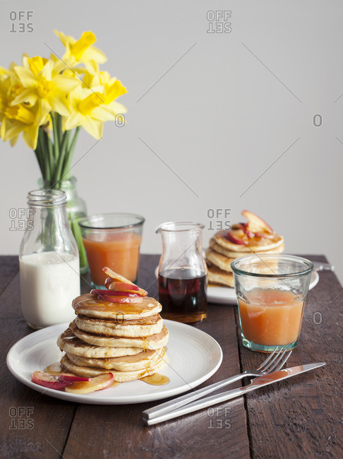 Stack of American pancakes with caramelized apple and maple syrup