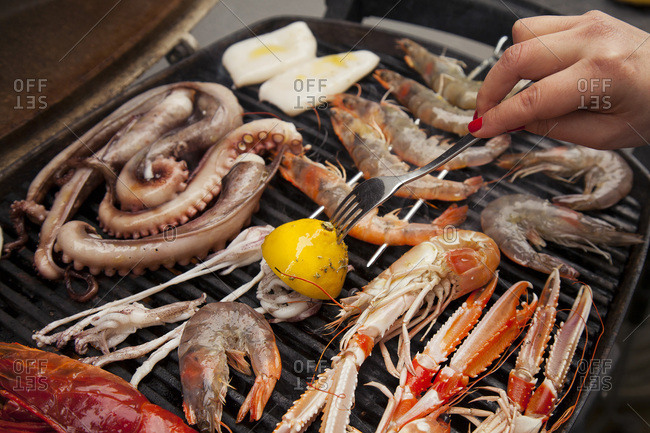 Basting seafood on a BBQ with marinated lemon