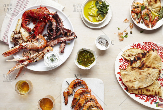 Tables cape featuring platters of fresh seafood and flatbread