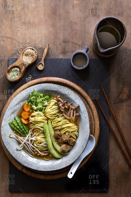 Vegan Japanese Ramen soup with avocado, sesame tofu and mushrooms in grey bowl over wooden background