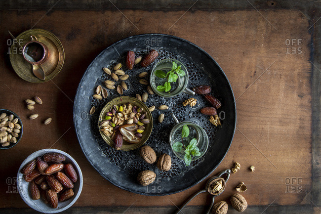 Healthy teatime oriental style with mint tea, dates, walnuts and pistachios  on black ornamental tray over wooden background with copy space