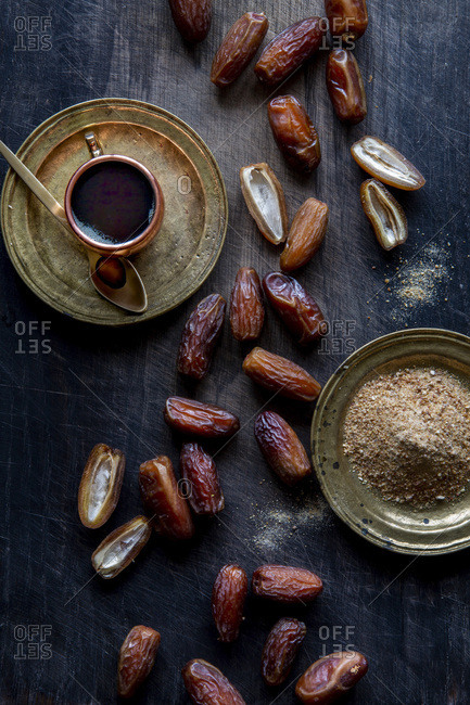 Dry dates, date sugar and date syrup over black wooden background