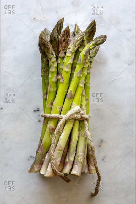 Bundle of fresh green asparagus on white marble board with copy space