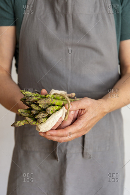Man in grey apron before white background holding a bundle of green asparagus wrapped in a towel in his hands