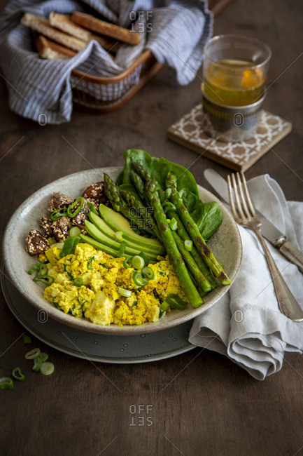 Vegan breakfast bowl with scrambled  tofu, green asparagus, sesame-coated mushrooms, avocado and spinach in stoneware bowl on laid wooden table with blur