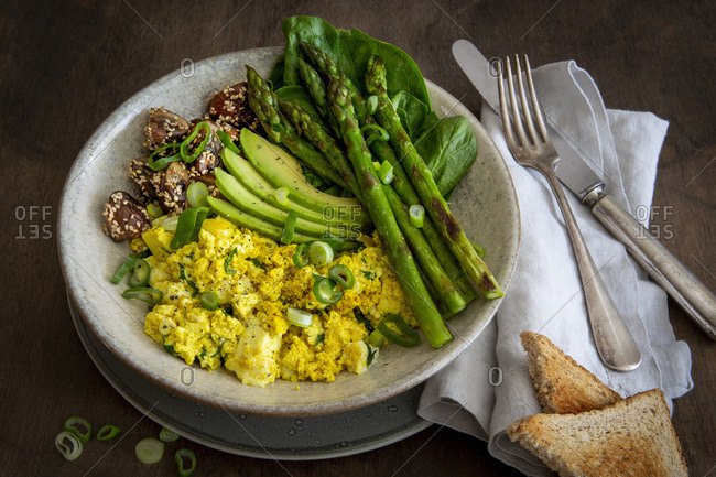 Vegan breakfast bowl with scrambled  tofu, green asparagus, sesame-coated mushrooms, avocado, spinach and toast in stoneware bowl on wooden table