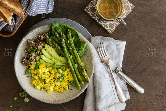 Vegan breakfast bowl with scrambled  tofu, green asparagus, sesame-coated mushrooms, avocado and spinach in stoneware bowl on laid wooden table with copy space