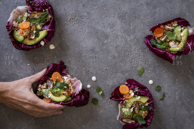 Man's hand taking one of several healthy, eatable radicchio bowls with couscous , avocado, dates. carrots, cucumber , herbs and sesame seeds over grey concrete background with copy space