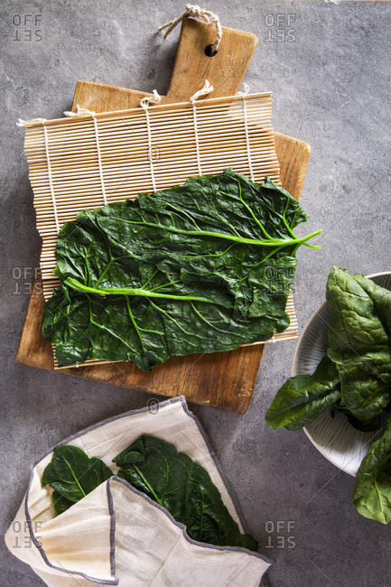 Vegan maki sushi with spinach coating in the making on wooden board over grey concrete background