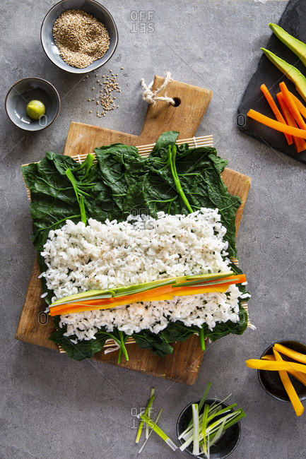 Spring like vegan maki sushi in the making with spinach, avocado, carrots, mango and shallots on wooden board over grey concrete background