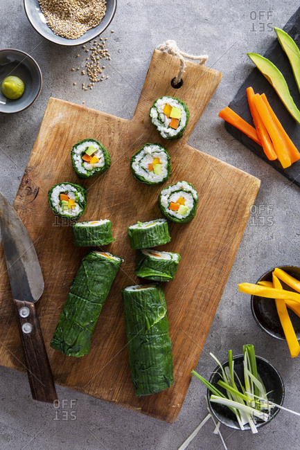Spring like vegan maki sushi with spinach, avocado, carrots, mango and shallots on wooden board over grey concrete background