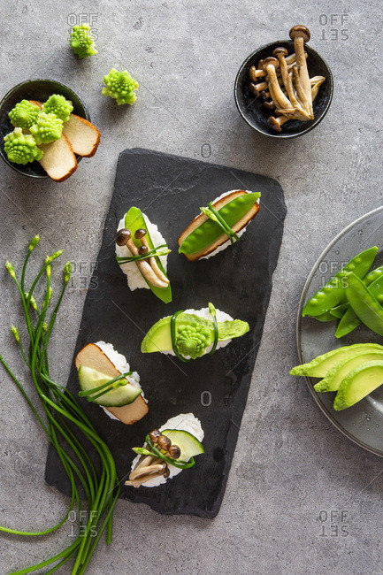 Spring like vegan nigiri sushi with smoked tofu, mushrooms and vegetables on white marble board over grey concrete background