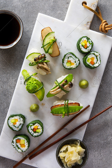 Spring like vegan maki and nigiri sushi with smoked tofu, mushrooms, fresh fruit and vegetables on white marble board over grey concrete background