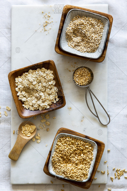 Oat grains, rolled oats and oat grist in wooden bowls on white marble board over white background