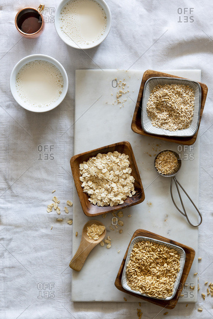 Oat grains, rolled oats, oat grist and oat milk in wooden bowls and white cups on white marble board over white background