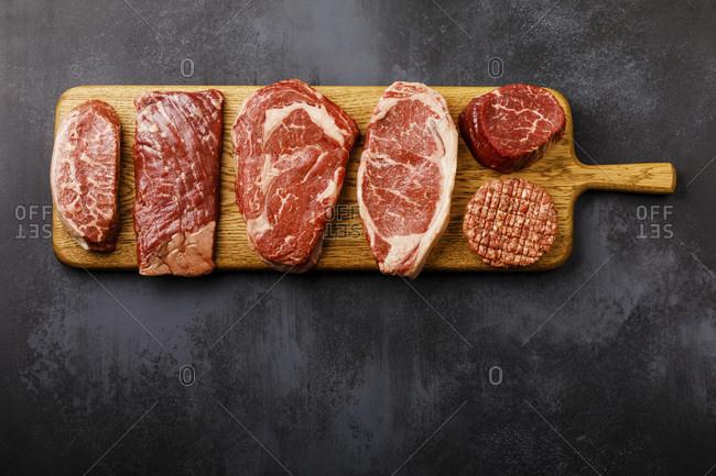 Variety of Raw Black Angus Prime meat steaks Top Blade, Machete, Rib Eye, Strip loin, Tenderloin fillet Mignon, Cutlet Burger on wooden board on dark background