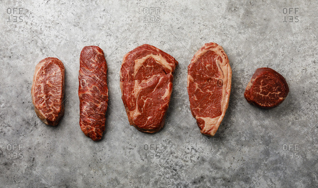 Variety of Raw Black Angus Prime meat steaks Top Blade, Denver, Rib Eye, Strip loin, Tenderloin fillet Mignon on gray background