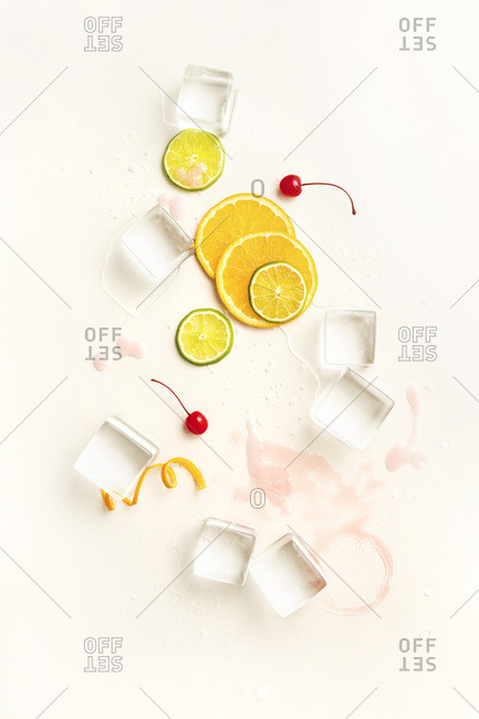Overhead layout of minimal cocktail ingredients including large ice cubes, orange and lime wheels, twists and cherries on pale yellow surface.
