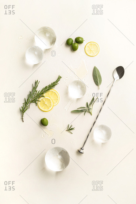 Overhead layout of minimal cocktail ingredients including large ice spheres, lemon wheels, herbs and olives on pale yellow surface.