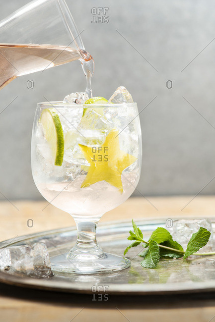 White Sangria with star fruit, lime and mint on a metal tray.