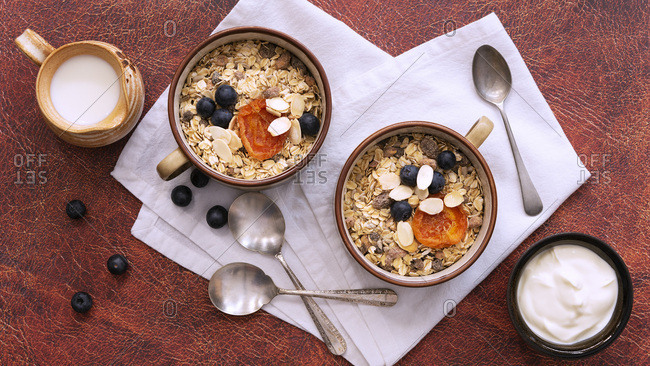 Breakfast setting, two servings of natural bircher muesli with dried apricots; blueberries and slithered almonds, a jug of milk and a bowl of yoghurt.