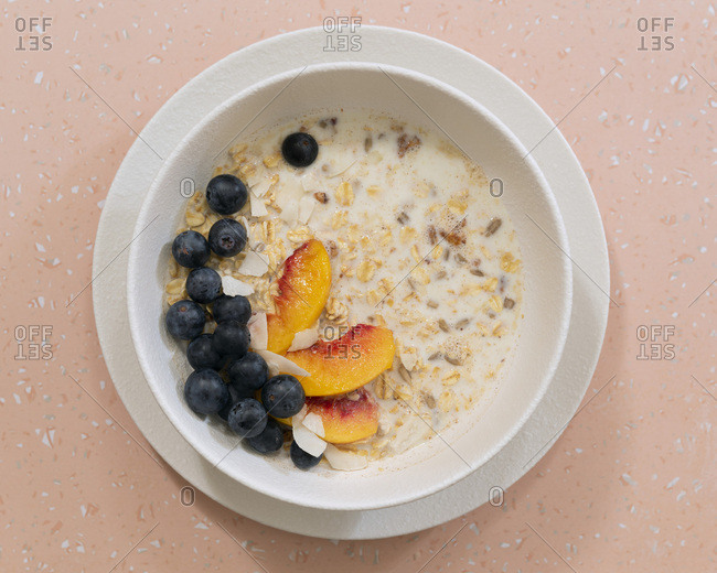A bowl of breakfast oats with blueberries, peach slices and coconut flakes on a pink background.