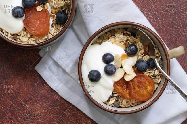 Healthy breakfast of bircher muesli, dried apricots, blueberries and yogurt in breakfast mugs.