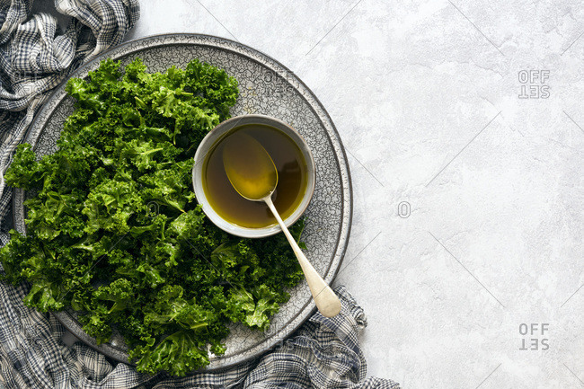 A bowl of spicy dressing amongst pieces of kale leaves coated with dressing on a platter. Copy Space.