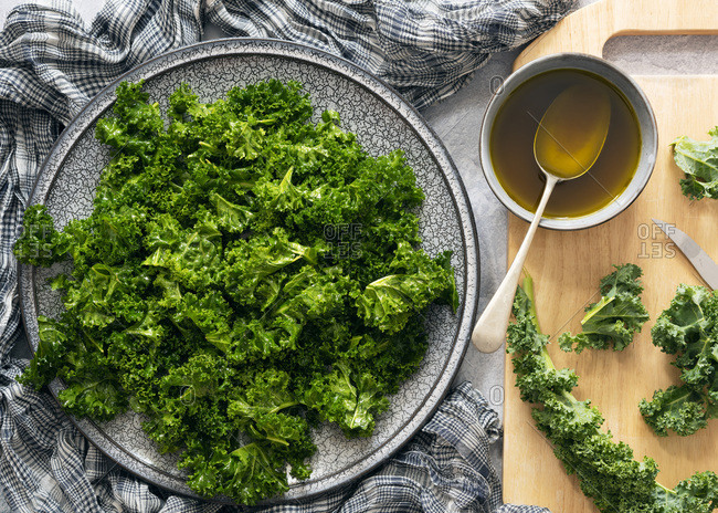 Preparation of kale salad with leaves broken up and coated in dressing.