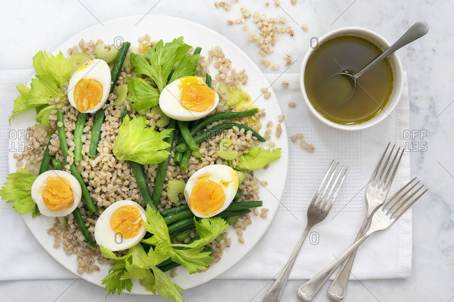 Bean, barley and egg salad with forks and a bowl of dressing.