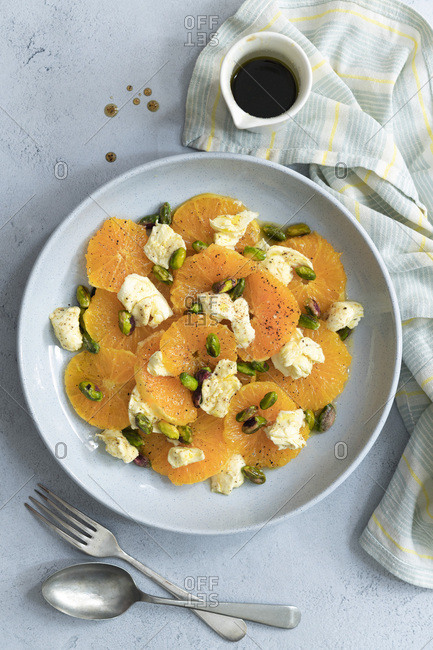 Orange and bocconcini salad with a spicy dressing and pistachio nuts.