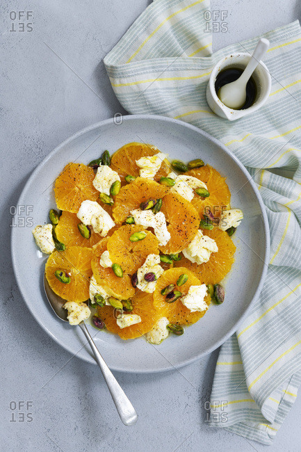 Orange, bocconcini and pistachio nut salad with a jug of spicy dressing.