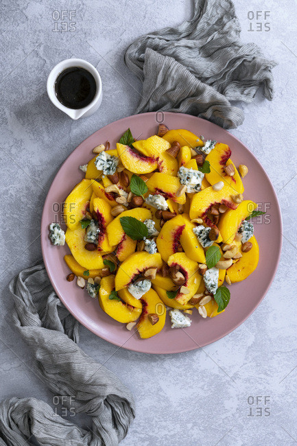 Peach salad, sliced peaches, blue vein cheese and mixed nuts with a jug of spicy dressing.