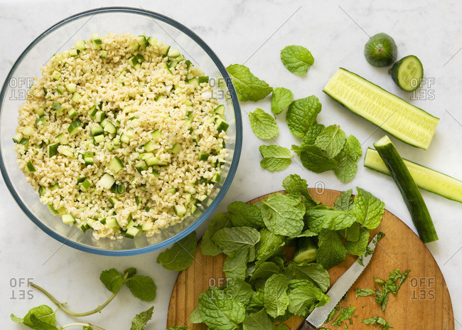 Preparation of cucumber tabouli salad. Mint leaves cut on a wooden board.